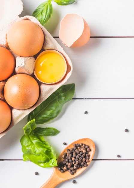 Eggs in carton with basil leaf and peppercorn on wooden plank Free Photo