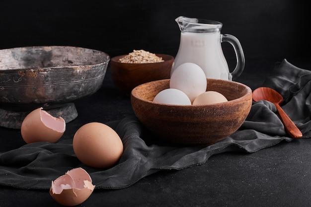 黒いbackgorundに牛乳の瓶と木製のカップの卵。 無料写真