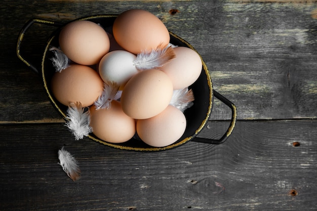 Eggs in a pot with feathers top view on a dark wooden background Free Photo