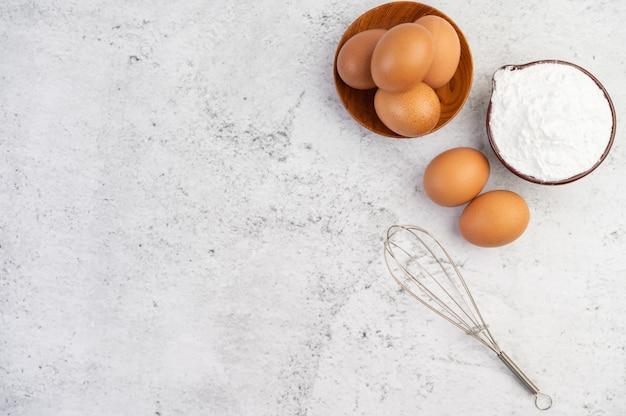 Uova, farina di tapioca in una tazza e frullino per le uova. Foto Gratuite