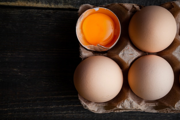Eggs with broken one top view on a dark wooden background space for text Free Photo