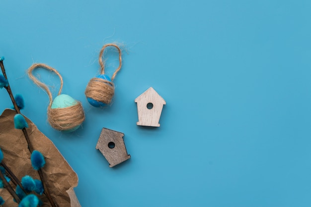 Eggs with threads near willow twigs and ornamental bird house Free Photo