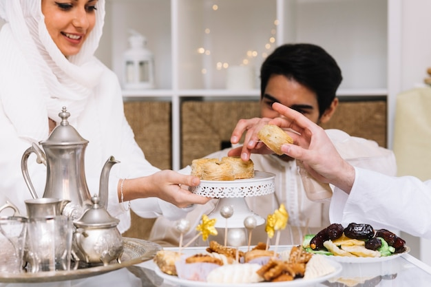 Eid al-fitr concept with people eating at table Free Photo