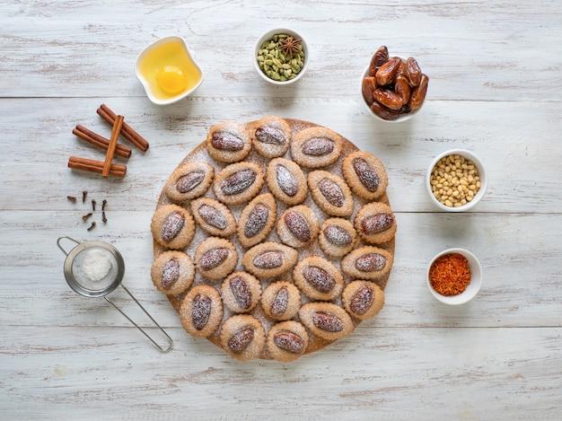 木製のテーブル、上面にeidデートのお菓子。 Premium写真