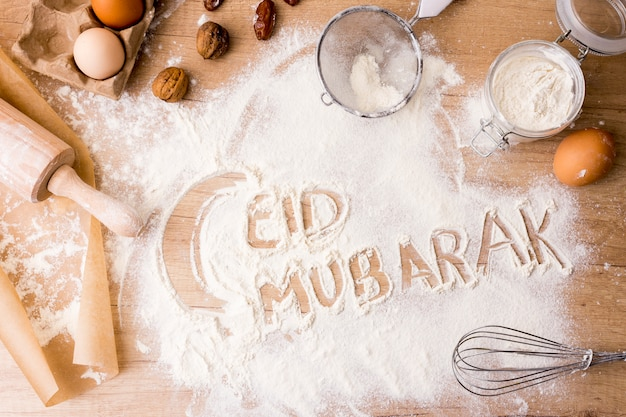 Eid mubarak inscription on flour with rolling pin Free Photo