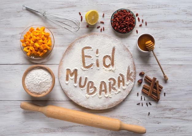 Ид мубарак - исламский праздник приветствие фраза «с праздником», приветствие зарезервировано. арабский фон выпечки. Premium Фотографии