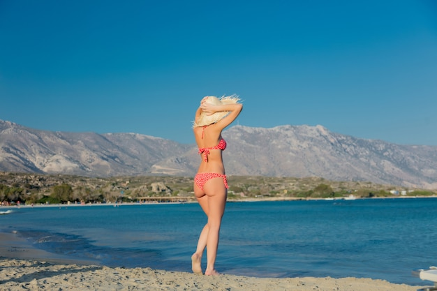 帽子とelafonissiビーチでビキニの女の子 Premium写真