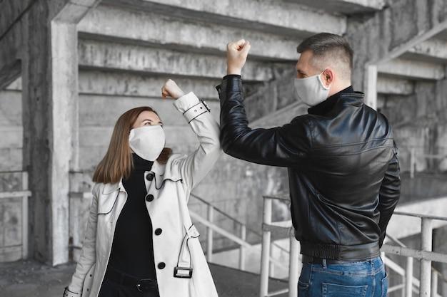 肘のバンピング。コロナウイルスの蔓延を回避する新しい挨拶方法covid19。男と女が抱擁や握手ではなく肘をぶつける Premium写真