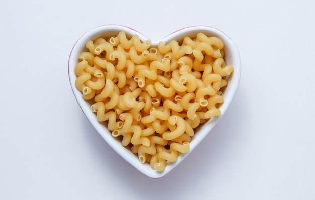 Elbow macaroni pasta in a heart shaped bowl top view on a white table Free Photo