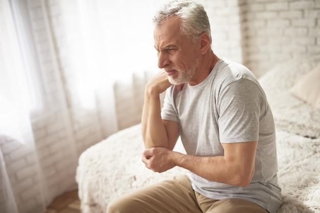 Elbow pain in morning old man suffering arthritis. Premium Photo