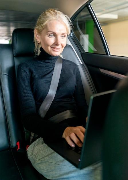 車でラップトップに取り組んでいる高齢者ビジネス女性 無料写真