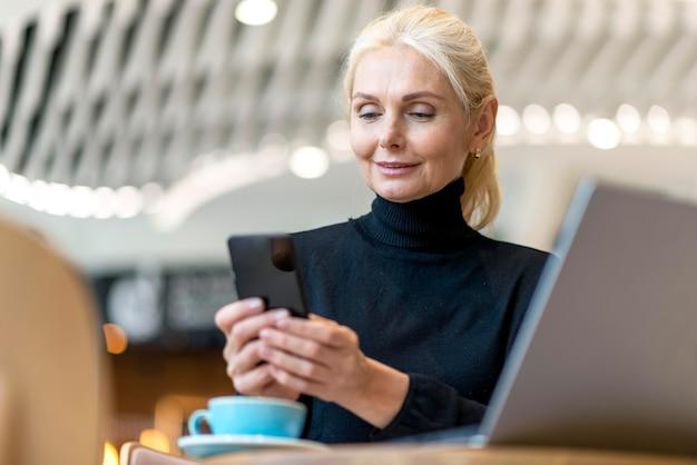 Старшая деловая женщина, работающая на смартфоне и ноутбуке Бесплатные Фотографии