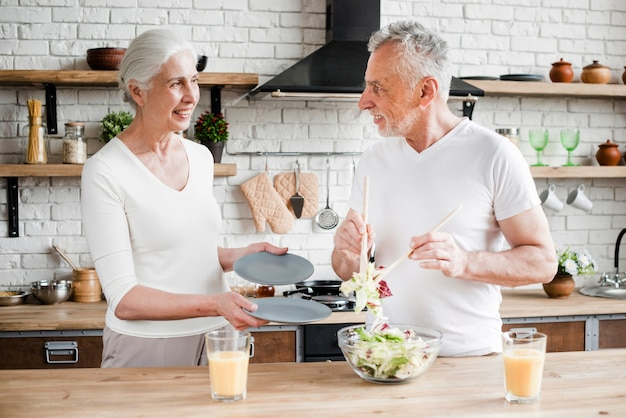 Elder couple cooking in the kitchen Free Photo