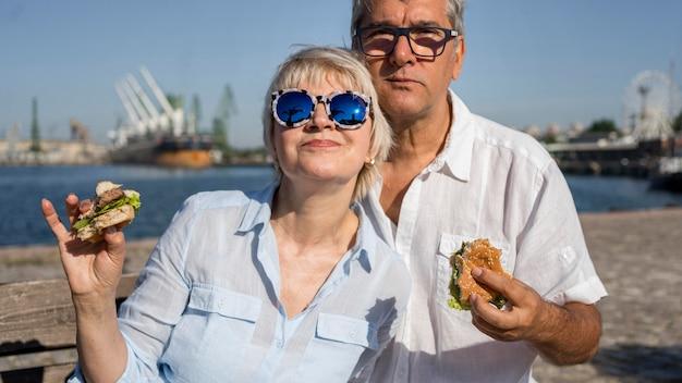 Elder couple enjoying a burger outdoors together Free Photo