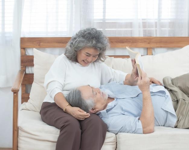 Пожилая пара сидит на диване и читает книгу дома Premium Фотографии
