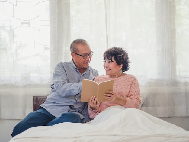 Elder couple sitting reading a book together in bed Premium Photo