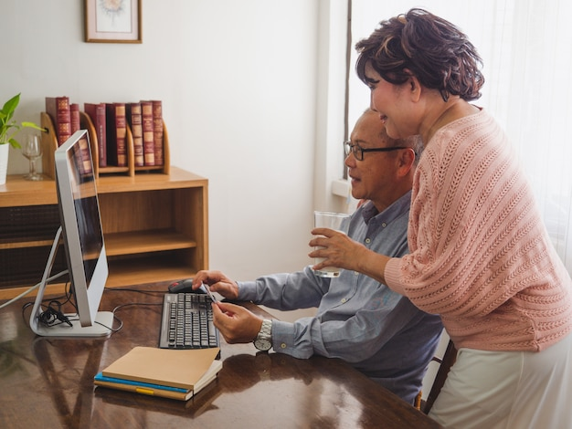 Elder couple using computer together at home Premium Photo