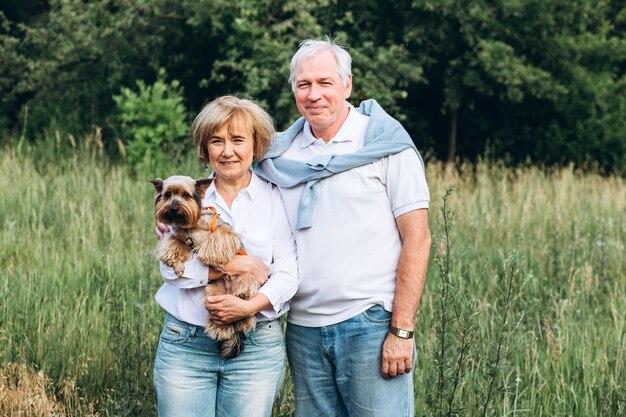 Пожилая пара гуляет на природе с маленькой собачкой Premium Фотографии
