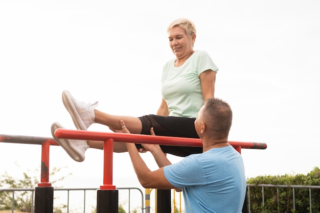 Elder couple working out together outdoors in the park Free Photo