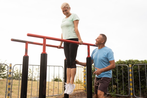 Elder couple working out together in the park Free Photo