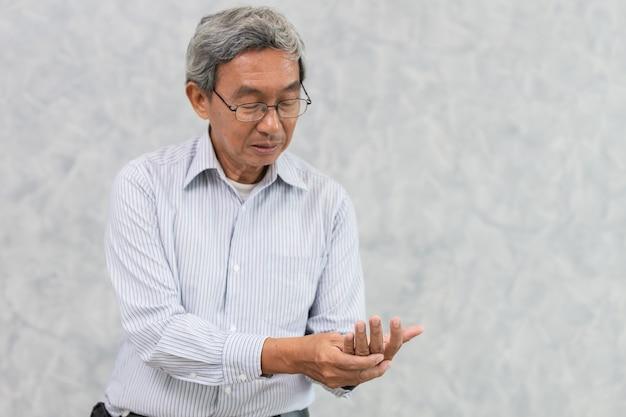 Боль в руке пожилого человека при ревматоидном артрите или триггере пальца. Premium Фотографии
