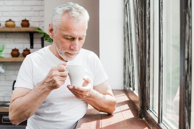 Elder man having a coffee Free Photo
