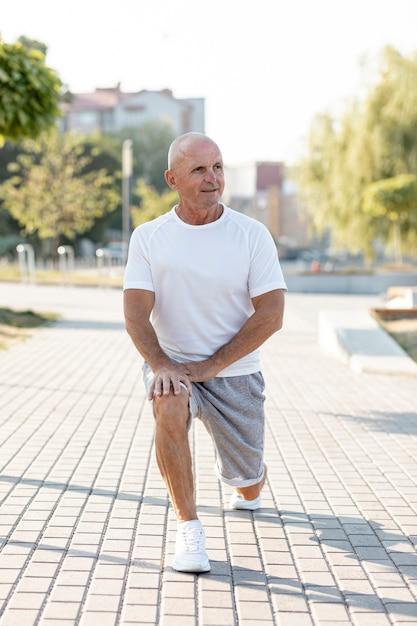 Elder man stretching out outdoors Free Photo