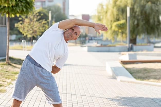 Elder man stretching on a sidewalk Free Photo