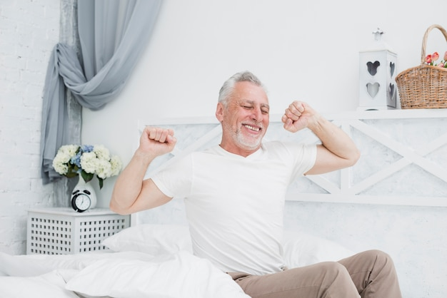 Elder man waking up in the bed Free Photo