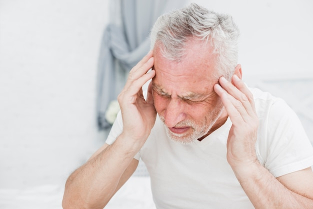 Elder man with a headache Free Photo