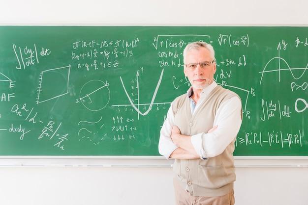Elder professor standing near chalkboard in classroom Free Photo