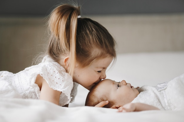 Elder sister is kissing little baby girl in the forehead with closed eyes Free Photo