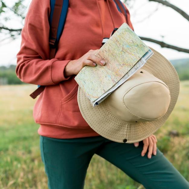 Cappello e mappa della tenuta della donna turistica più anziana Foto Gratuite