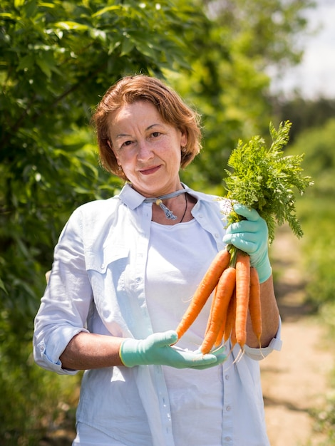 Elder woman holding fresh carrots in her hand Free Photo