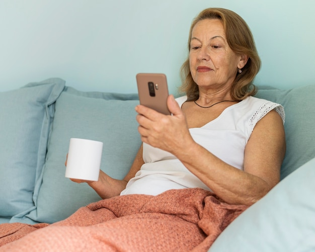 Elder woman at home during the pandemic enjoying a cup of coffee and using smartphone Free Photo