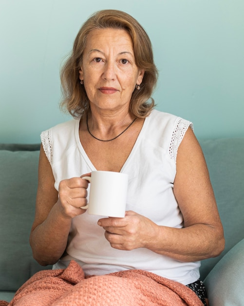 Elder woman at home during the pandemic enjoying a cup of coffee Free Photo