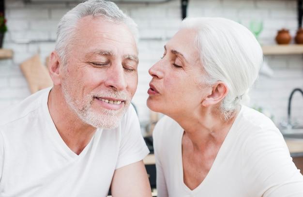 Elder woman kissing her husband Free Photo