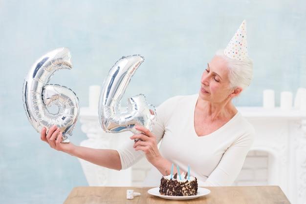 La donna più anziana che guarda l'aerostato della stagnola d'argento sul suo sessantesimo compleanno Foto Gratuite