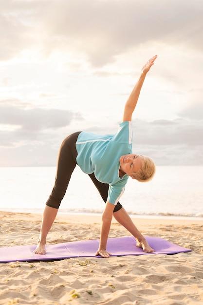 Пожилая женщина упражнениями йоги на пляже Бесплатные Фотографии