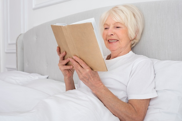 Elder woman reading a book in the bedroom Free Photo
