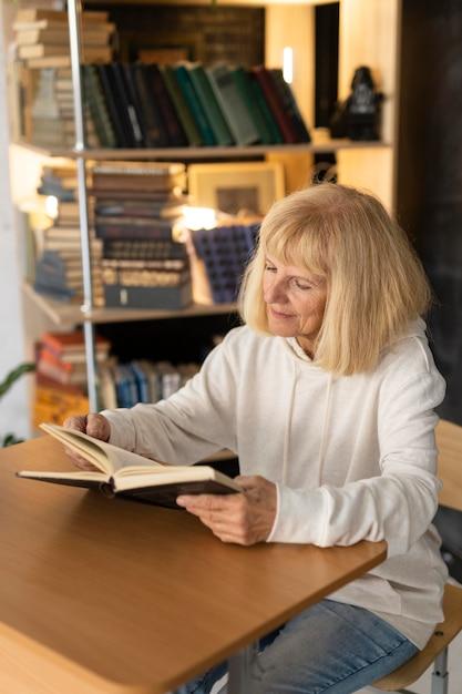 Donna anziana che legge un libro a casa Foto Gratuite