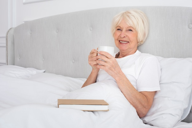 Elder woman reading a cup in the bedroom Free Photo