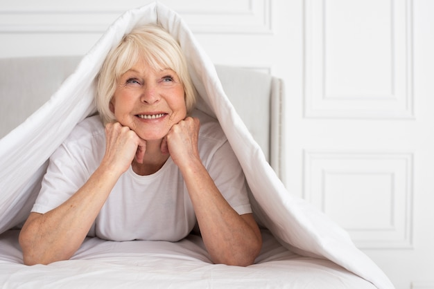 Elder woman sitting under blanket Free Photo