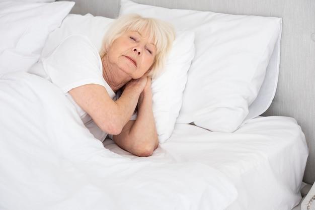 Elder woman sleeping in her bed Free Photo