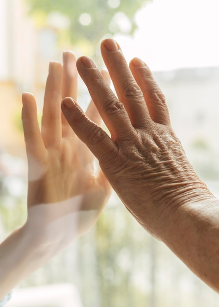 Elder woman touching hand with someone through window during the pandemic Free Photo