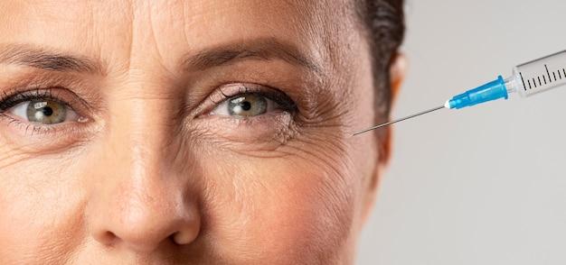 Пожилая женщина с помощью инъекций от морщин вокруг глаз Бесплатные Фотографии