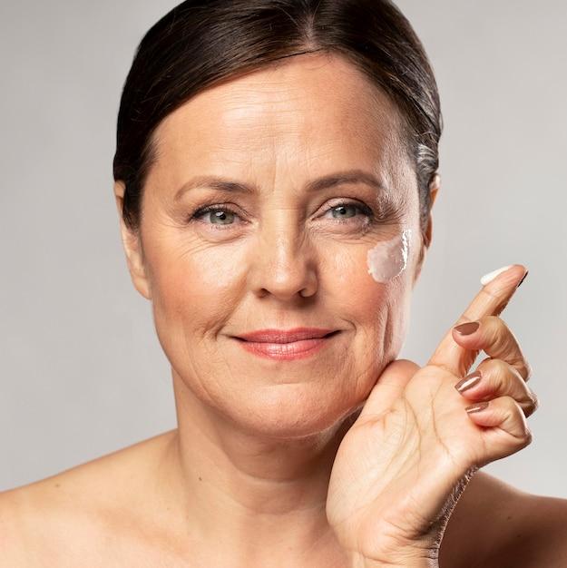 Donna anziana che utilizza crema idratante sul viso Foto Gratuite