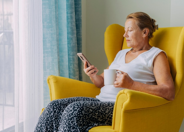 Elder woman using smartphone at home during the pandemic while having coffee Free Photo