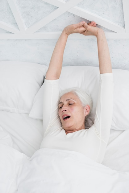 Elder woman waking up in the bed Free Photo