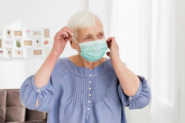 Elder woman wearing medical mask at home Free Photo